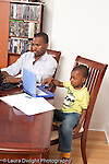 3 year old boy at home with his father modeling imitation father working on paperwork from job and using laptop computer boy using toy computer vertical