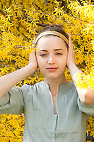 Young woman covering her ears standing amoungst Forsythia flowers