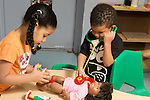 Education preschool 4 year olds boy and girl giving medical attention to doll girl giving shot and boy listening with stethoscope