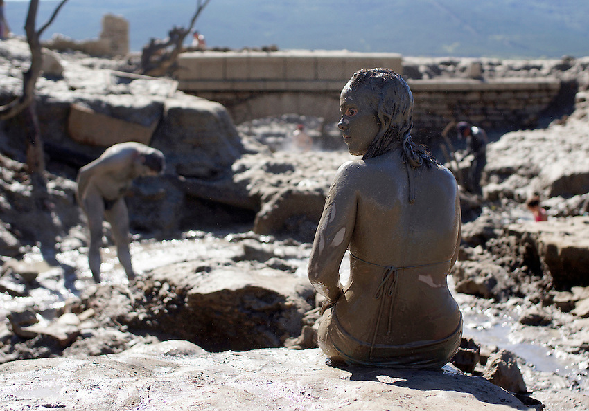 A girl covered in mud reposes in the ancient Baths of sulphurous waters of Tiermas on October 13, 2012, in the Spanish reservoir of Yesa. The ancient baths of sulphurous waters of Tiermas are under Yesa reservoir waters and return to the surface when the reservoir is running low on water.  Photo: Ander Gillenea