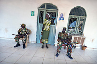 Soldiers guard the entrance of the Governor's office. Pictures of John Garang and Slava Kirr, President of Southern Sudan are taped to the wall. Former rebel commanders are now presidents and governors. South Sudan.