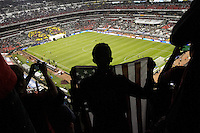 A USA fan holds an American flag while the US Men's National team takes the field for warmups at Azteca stadium before the USA vs. Mexico World Cup Qualifier in Mexico City, Mexico on March 26, 2013.