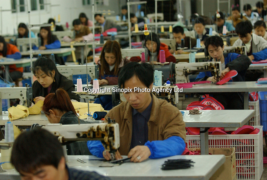 """Workers at General Union Stationary & Gift Co. Ltd, make """"cool Dog"""" bags at a Taiwanese-owned factory on the outskirts of Fuzhou City, China..02-MAR-04"""