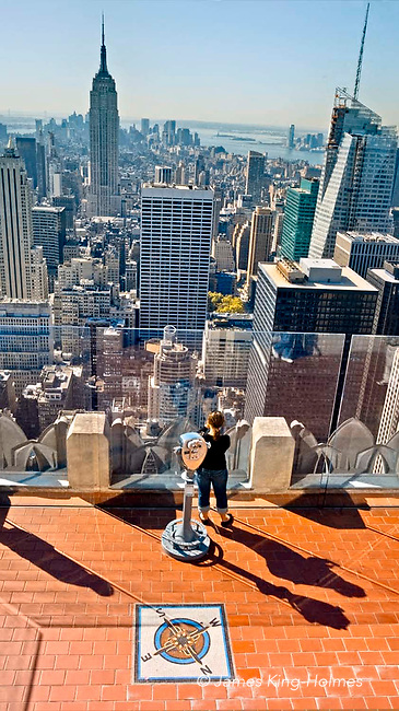 Tourist photographs Manhattan from exterior viewing platform at the top of the Rockefeller Centre, New York.