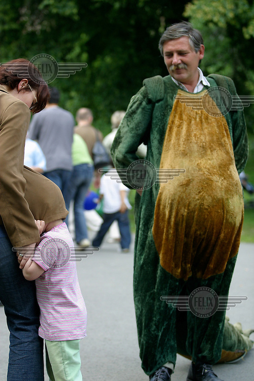 Child hides under mothers jacket upon seeing a man in dragon costume.
