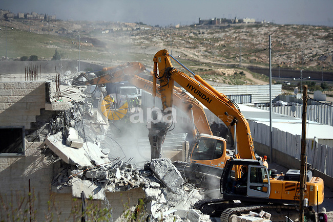 bulldozers Israeli demolish a house, belonging to a Palestinian family in Khallat al-Ein square in the al-Tur neighborhood east of the Old City of Jerusalem, on March 26, 2014. Israel rarely grants Palestinians permits to build in the West Bank, including East Jerusalem. It has demolished at least 27,000 Palestinian homes and structures since occupying the West Bank in 1967, according to the Israeli Committee Against House Demolitions. Photo by Saeed Qaq