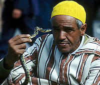 In Marrakesh, a Moroccan man holds snake