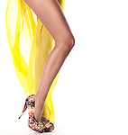 Sexy long legs of a young woman wearing yellow summer beach dress and high heel shoes isolated on white background Image © MaximImages, License at https://www.maximimages.com