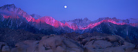 902000001 panoramic view of a full moon setting over mount whitney and the eastern sierras lit by pre-dawn alpenglow with the spectacular granite boulders of the alabama hills blm protected lands in the foreground in kern county california