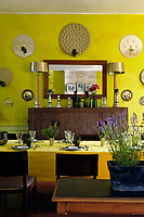 The dining room has been painted a very untraditional lime-green and the walls are covered in mirror-backed circular sconces