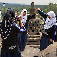 "Borobudur, Java, Indonesia.  Young Indonesian Women Visiting the Temple.  ""Proud to be Moslem"" Written on their Clothing."