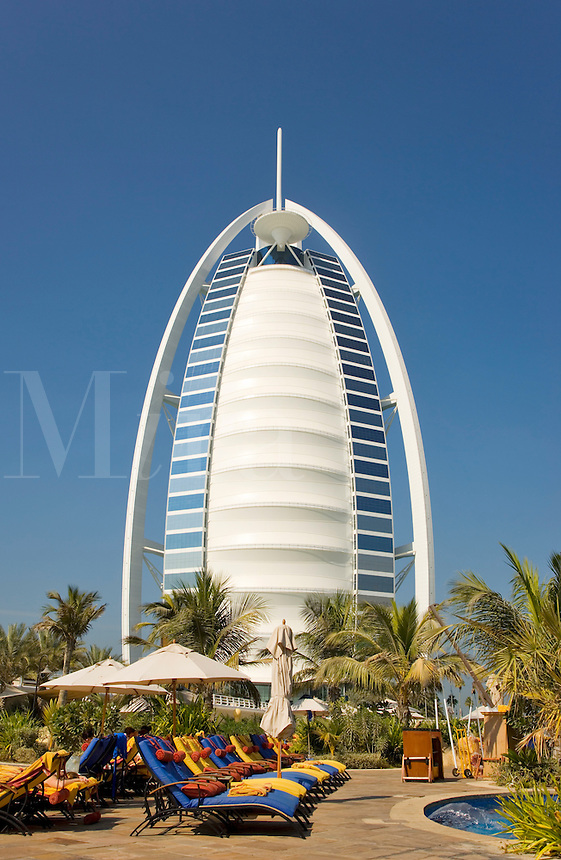 Dubai.  View of Burj al Arab Hotel over executive pool area and gardens of Jumeirah Beach Hotel..