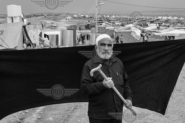 Ahmed (name changed to protect his identity), 70, poses for a portrait in the Domiz refugee camp in the Kurdistan Region of Iraq. Ahmed fled Syria with his wife and eight of their nine children approximately four months before this photograph was taken, when their family home in Damascus was destroyed in an attack. Together with four other families - 50 people in all - they escaped in the back of an open-topped truck after covering themselves with plastic sheeting. Many hours later they arrived in Derik City, where they spent 20 days before continuing on to the Iraqi border. Ahmed's one son who remained behind was killed in late October 2012. Following an explosion, he ran into the street to help an injured friend, only to be killed in a second blast..The most important thing Ahmed was able to bring with him is the cane he holds in this photograph. Without it, he says, he would not have made the two-hour crossing on foot to the Iraqi border. 'The only other thing I have left is this finger,' he said. 'All I want now is for my family to find a place where they can be safe and stay there forever. Never should we need to flee again.'