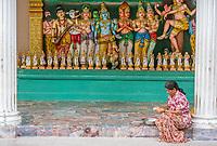 Worshiper Preparing Offerings as Hindu Deities Line the Wall, Sri Mahamariamman Hindu Temple, Kuala Lumpur, Malaysia.