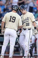 Vanderbilt Commodores outfielder Pat DeMarco (18) celebrates with teammate Stephen Scott (19) after hitting a home run against the Michigan Wolverines during Game 3 of the NCAA College World Series Finals on June 26, 2019 at TD Ameritrade Park in Omaha, Nebraska. Vanderbilt defeated Michigan 8-2 to win the National Championship. (Andrew Woolley/Four Seam Images)