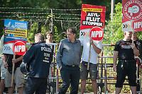 """29 Neonazis von NPD und Autonomen Nationalisten aus Berlin und Brandenburg protestieren in Berlin-Weissensee gegen eine geplante Fluechtlingsunterkunft.<br /> Aufgrund einer Auflage der Polizei durften sie nicht vor dem Gebaeude stehen, sondern mussten einige Meter weiter vor einem Brachgelaende Aufstellung nehmen.<br /> Ca. 100 Menschen protestierten gegen die Neonazi-Kundgebung.<br /> In der Bildmitte mit kariertem Hemd: Uwe Meenen, wegen Volksverhetzung verurteilte NPD-Kader.<br /> Rechts: Romano Subke, Neonazi aus Hellersdorf, mit T-Shirt """"Weisse Woelfe Terrormachine"""".<br /> 9.8.2014, Berlin<br /> Copyright: Christian-Ditsch.de<br /> [Inhaltsveraendernde Manipulation des Fotos nur nach ausdruecklicher Genehmigung des Fotografen. Vereinbarungen ueber Abtretung von Persoenlichkeitsrechten/Model Release der abgebildeten Person/Personen liegen nicht vor. NO MODEL RELEASE! Don't publish without copyright Christian-Ditsch.de, Veroeffentlichung nur mit Fotografennennung, sowie gegen Honorar, MwSt. und Beleg. Konto: I N G - D i B a, IBAN DE58500105175400192269, BIC INGDDEFFXXX, Kontakt: post@christian-ditsch.de<br /> Urhebervermerk wird gemaess Paragraph 13 UHG verlangt.]"""