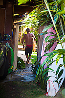 Surfer Robin Johnson carrying a surfboard through a wooden gate at a North Shore home on Oahu