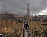 A man passes a ruined gutter of irrigation canal. Since the collapse of the Soviet Union irrigation system in Kyrgyzstan fell into decay. Many channels are destroyed and not used for it's purposes. Kyrgyzstan. 2012