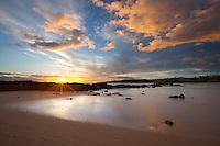 The sun hits the horizon at Salt Pond in Hanapepe on Kauai's west side