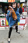 Apr 04, 2010 - Kawasaki, Japan - A  woman holds a wooden phallic figure during the Kanamara Matsuri (Festival of the Steel Phallus) held in Wakamiya Hachimangu Shrine on April 4, 2010 in Kawasaki, Japan. The annual feritility festival, held traditionally the first Sunday in April, is said to encourage fertility and bring harmony to married couples. The festival has also become somewhat of a tourist attraction and is used to raise money for HIV research and awareness of AIDS prevention.