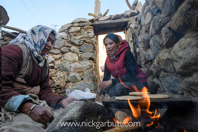 Baking kulcha (flat bread) on traditional open fire for consumption in an ecotourism lodge.  Part of a broader eco tourism initiative to augment their income and change local attitudes towards snow leopards. Ulley Valley, Himalayas, Ladakh, northern India.