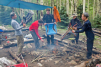 Photo story of Philmont Scout Ranch in Cimarron, New Mexico, taken during a Boy Scout Troop backpack trip in the summer of 2013. Photo is part of a comprehensive picture package which shows in-depth photography of a BSA Ventures crew on a trek.  In this photo BSA Venture Crew Scouts use their ultralite backpacking chairs to fan the flames as they worked to get a fire started after heavy rains flooded the campsite in Baldy Town at Philmont Scout Ranch.   <br /> <br /> The  Photo by travel photograph: PatrickschneiderPhoto.com