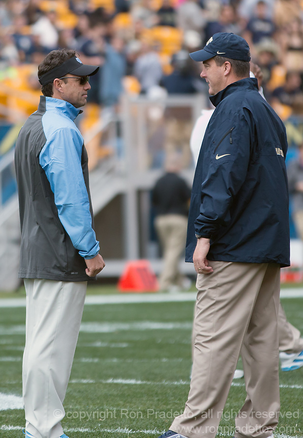 North Carolina head coach Larry Fedora (left) and Pitt head coach Paul Chryst meet before the game. The North Carolina Tar Heels defeated the Pitt Panthers 34-27 at Heinz Field, Pittsburgh Pennsylvania on November 16, 2013.