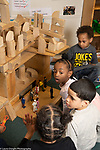 Education preschool 4 year olds group of children boys and girls playing with large structure they built from wooden blocks, playing with dolls inside the environment