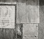 Scan of vintage print. Shed side with aged and cracked asphalt siding. 1980's. 1 of 1;