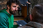 Balkan Lynx (Lynx lynx balcanicus) biologist, Alexander Pavlov, checking camera trap photos with former hunter turned conservationist, Plumb Mustafa, with biologists, Lilli Middelhoff and Eko Veapi, maintaining box trap, Mavrovo National Park, North Macedonia
