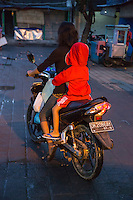 Bali, Indonesia.  Little Boy on his Mother's Motorbike.  Jimbaran Fish Market, Early Morning, no Helmet.