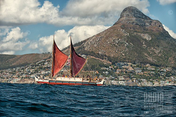 """Voyaging canoe Hokule'a sails toward Cape Town, South Africa, with Lino's Head (mountain peak) in the distance, Thursday, November 12, 2015. Hokule'a was on a """"Malama Honua"""" (Care for the Earth) worldwide voyage to raise awareness about the importance of protecting the world's oceans, considered the greatest environmental challenge of our time."""