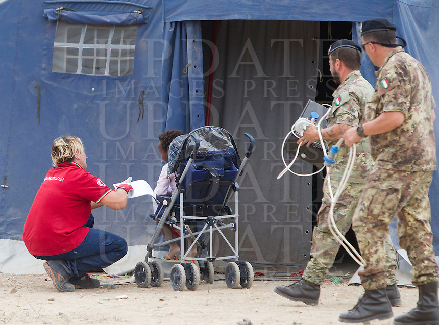 Un'operatrice della Croce Rossa gioca con una bambina nella tendopoli allestita presso la stazione Tiburtina a Roma, 16 giugno 2015.<br /> A health workers of the Italian Red Cross plays with a child in the tent camp set up near the Tiburtina railway station in Rome, 16 June 2015. Italy is facing a huge flow of migrants brought to Sicily after rescue at sea, many of whom are trying to join their relatives in northern Europe. <br /> UPDATE IMAGES PRESS/Riccardo De Luca