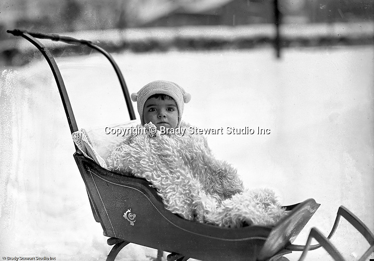 Product: Antique Child's Push Sleigh<br /> <br /> Wilkinsburg PA: Helen Stewart bundled in a blanket and hat while riding in a baby sleigh.