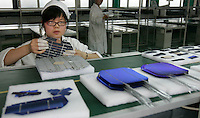 Solar powered photo-voltaic (PV) cells are assembled by workers at a factory owned by the Himin Group, the worlds largest manufacturer of solar thermal water heaters, which is based in Dezhou, Shandong Province, China. Dezhou, a city of 5.5 million people, is known as China's 'Solar Valley'. More than 90% of all households in the city use solar thermal water heaters. Ten cities in China have made it compulsory, or offered subsidies, for under twelve storey civil-use buildings, including residential, restaurants, and hotels to install solar thermal water heaters..