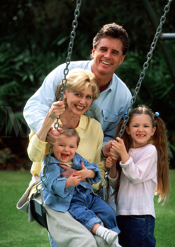 A smiling young family playing on a swing.