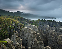 Moody sunrise over Pancake rocks, limestone formations on rugged coast in Punakaiki, Paparoa National Park, Buller Region, West Coast, New Zealand, NZ