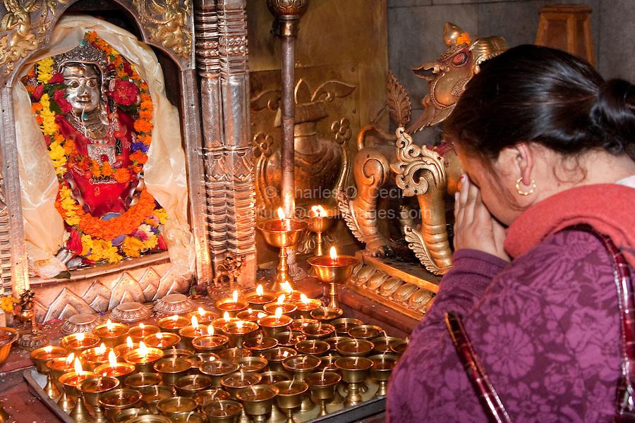 Bodhnath, Nepal.  Nepali Woman Praying at the Shrine to the Goddess Ajima, or Hariti, Goddess of Smallpox and Other  Diseases.