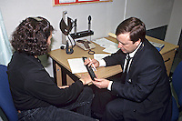 Police surgeon attending to a suspect at a police station. The suspect is involved in a serious crime and the doctor is taking a measurement of a bruise on her hand which may be used in evidence. This image may only be used to portray the subject in a positive manner..©shoutpictures.com..john@shoutpictures.com