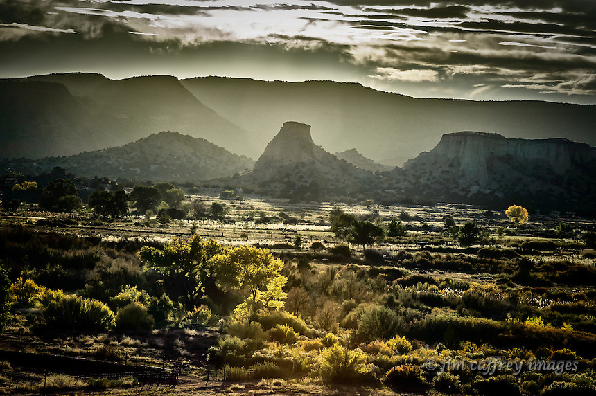 The sun shines through a veil of clouds  to backlight a butte at Jemez Pueblo in north-central New Mexico.