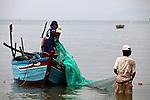 Fishermen pull a net into their boat in the flat sea off Mui Ne, Vietnam. Nov. 20, 2011.