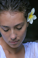 A portrait of a young local woman, eyes closed, with a yellow and white plumeria above her ear, Kaneo'he, O'ahu.