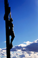 Statue of Jesus Christ on the cross against a cloudy sky.