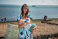 """A young woman with wind blown hair breastfeeding her baby while standing up on a beach.<br /> <br /> Image from the breastfeeding collection of the """"We Do It In Public"""" documentary photography picture library project: <br />  www.breastfeedinginpublic.co.uk<br /> <br /> <br /> Hampshire, England, UK<br /> 03 /09/2013<br /> <br /> © Paul Carter / wdiip.co.uk"""