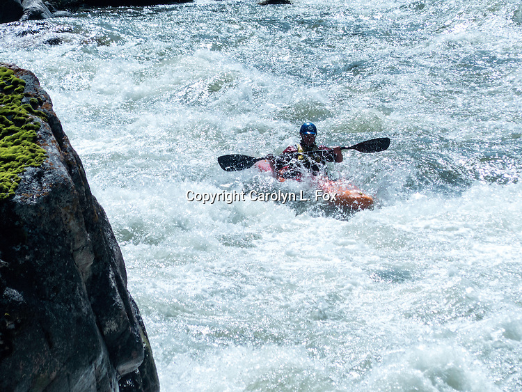 A man rides a kayak down the Gallatin River in Montana. People kayak on the Gallatin Rvier, between Big Sky and Bozeman, Montana.