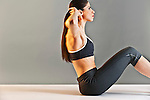 Young Caucasian woman wearing black sports clothing doing sit-ups in studio