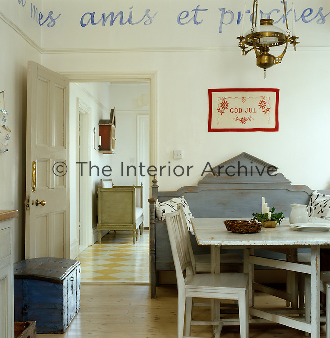 The dining area of the kitchen is furnished with a variety of Swedish antiques with a distressed paint effect