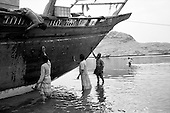 SuSur, Oman<br /> July 2001<br /> <br /> Indian workers clean and coat the underbelly of an older dhow.