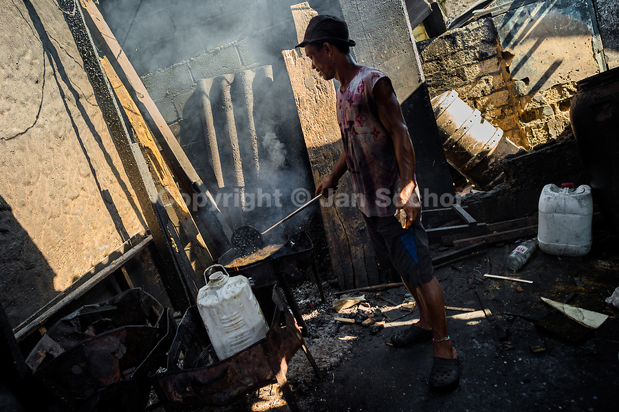 An Afro-Colombian cook fries fish in boiling oil in a street restaurant in the market of Bazurto in Cartagena, Colombia, 6 December 2018. Far from the touristy places in the walled city, a colorful, vibrant labyrinth of Cartagena's biggest open-air market sprawls to the Caribbean seashore. Here, in the dark and narrow alleys, full of scrappy stalls selling fruit, vegetables and herbs, meat and raw fish, with smelly garbage on the floor and loud reggaeton music in the air, the African roots of Colombia are manifested.