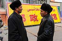CHINA, autonomous province Xinjiang, city Kashgar, where uyghur people are living , gentrification, new shop with big Han chinese and small uyghur letters / CHINA, Automome Provinz Xinjiang, Stadt Kashgar, hier lebt das Turkvolk der Uiguren, die durch massive Zuwanderung von Han Chinesen zur Minderheit werden, Gentrifizierung, Schild fuer ein neues Geschaeft, grosse chinesische und kleine uigurische Schriftzeichen